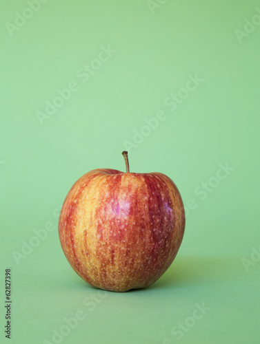 A Honey Crisp apple on a green background