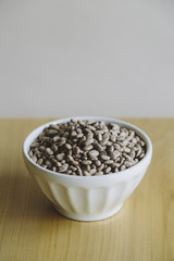 A white round china bowl of kidney beans on a table top.