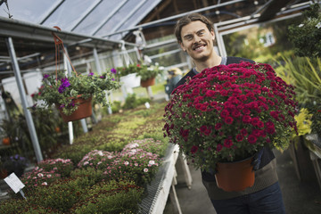 Organic Farmer at Work. A young man holding a large pot of flowering plants.