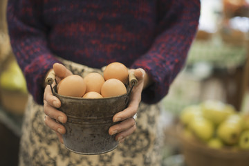 Organic Farmer at Work. A woman carrying a container of eggs.