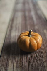 A small round pumpkin or squash vegetable with a bright orange skin, on a wooden tabletop.