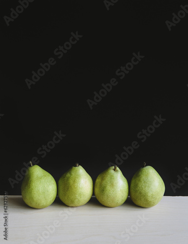 Row of four green Anjou pears, black background