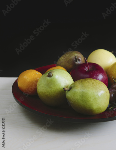 Plate of organic fresh fruit (tangerines, grapes, red bartlett pear, green anjou pears apples),