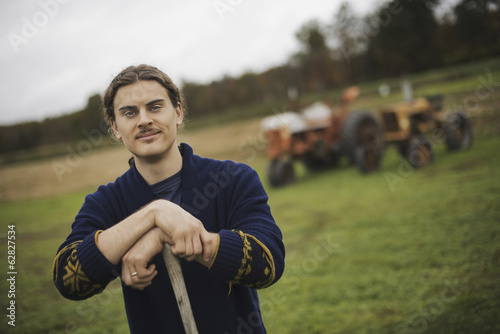 Organic Farmer at Work, A man leaning on a garden hoe. A tractor in the background.