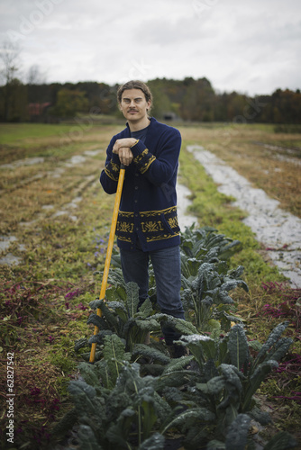 Organic Farmer at Work. A young man leaning on a long handled garden hoe, among the crops.