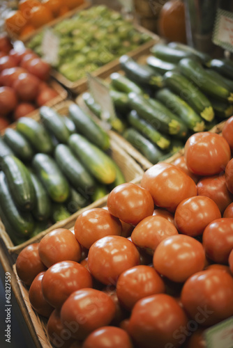 A farm stand display of organic vegetables. Produce. tomatoes and cucumbers.