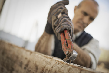 A man working in a reclaimed timber yard. Using a tool to remove metals from a reclaimed piece of timber.