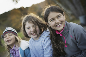 Three young girls, children, outside in the fresh air. Autumn foliage.