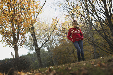 Autumn foliage on the trees on a farm. A young girl in a red knitted jumper with a warm tartan woolly hat.