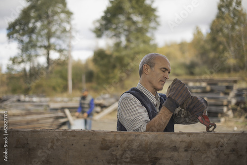 Two men working in a reclaimed timber yard. One using a tool to remove metals from a reclaimed piece of timber.