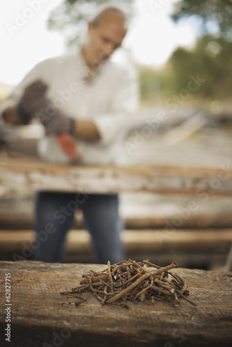 A man working in a reclaimed timber yard. Using a tool to remove metals from a reclaimed piece of timber. A heap of rusty metal nails.