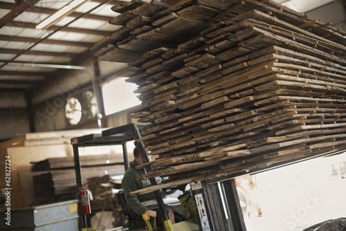 A heap of recycled reclaimed timber planks of wood being moved on a forklift truck. Environmentally responsible reclamation in a timber yard.