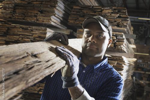 A heap of recycled reclaimed timber planks of wood. Environmentally responsible reclamation in a timber yard. A man carrying a large plank of splintered rough wood.