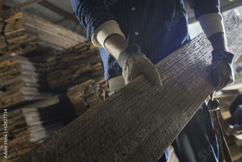 A heap of recycled reclaimed timber planks of wood. Environmentally responsible reclamation in a timber yard. A man carrying a large plank of wood.
