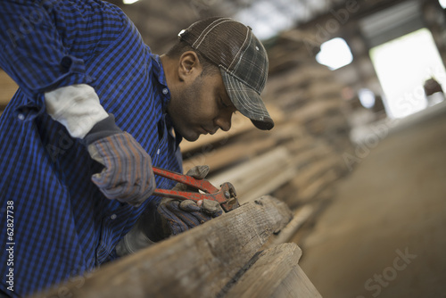 A man working in a reclaimed timber yard. Using a tool to remove metals from a reclaimed piece of timber. Workshop.