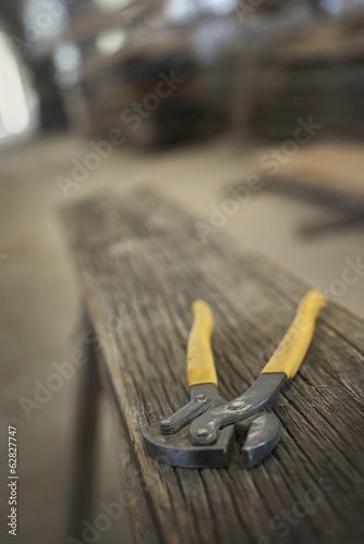 A heap of recycled reclaimed timber planks of wood. Environmentally responsible reclamation in a timber yard. A pair of pliers on a plank of wood.
