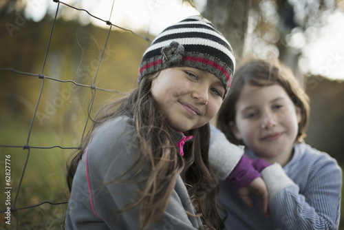 Two young girls side by side outdoors on a farm. Leaning on a fence post.