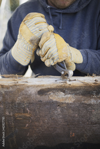 A reclaimed lumber workshop. A man preparing the timber by removing all the nails and studs.