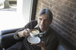 A man sitting in a coffee shop. Holding a cup of frothy  cappuccino coffee.