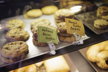 A tray of cookies, biscuits and baked goods on the counter at a coffee shop. Labels. Freshly home baked snacks.