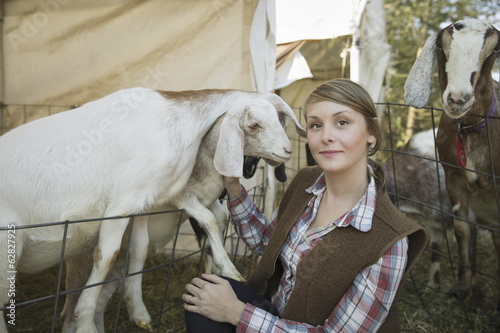 Goats in a pen leaning over the fences at a farm. A young woman tickling the chin of a white goat.