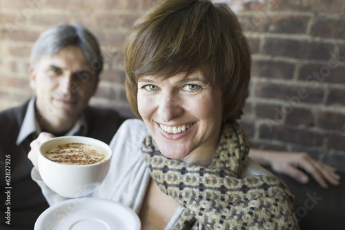 Two people sitting in a coffee shop. A man and woman, holding white china cups of cappuccino coffee.