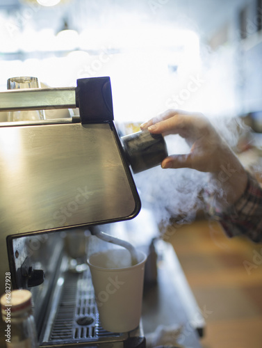A person, barista making coffee, and frothing milk using a steam pipe. Coffee shop.
