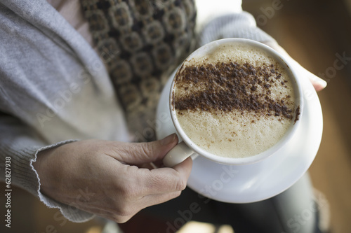 A person holding a full cup of frothy cappuccino coffee in a white china cup. Chocolate powder sprinkled in a pattern on the top. Coffee shop.
