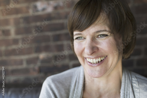 A woman in a coffee shop. Smiling. Head and shoulders.