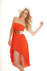 woman orange dress sun hat hand up out