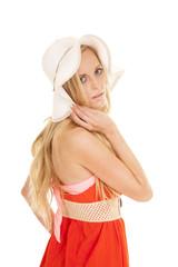 woman orange dress sun hat back look