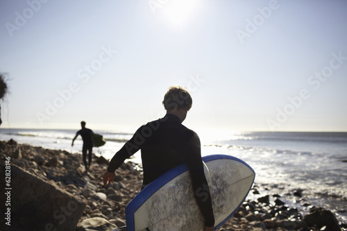 Two people in wetsuits on a beach, carrying their surfboards.
