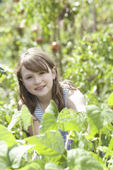 A young girl sitting in among the fresh green foliage of a garden. Vegetables and flowers. Picking fresh vegetables.