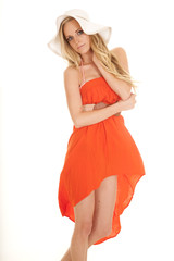woman orange dress sun hat skirt blowing