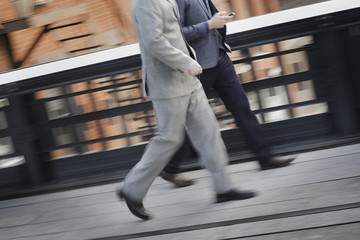 Two men in business clothes walking along a city sidewalk.