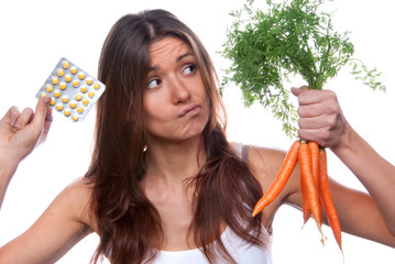 Woman choose between organic fresh carrots medical tablet pills