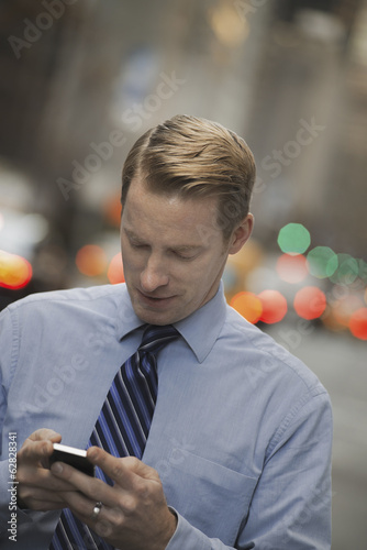 A man in a shirt and tie checking his cell phone, standing on a busy street.