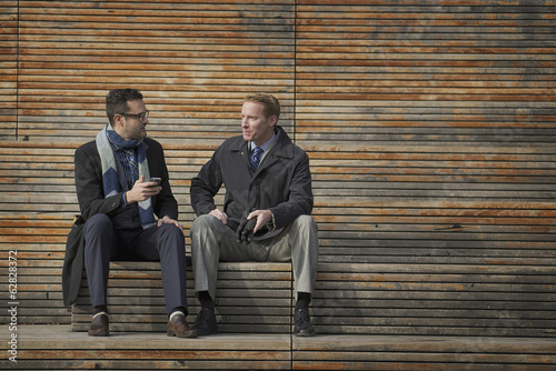 Two men sitting on a bench outside a large building in the city. One checking his mobile phone.