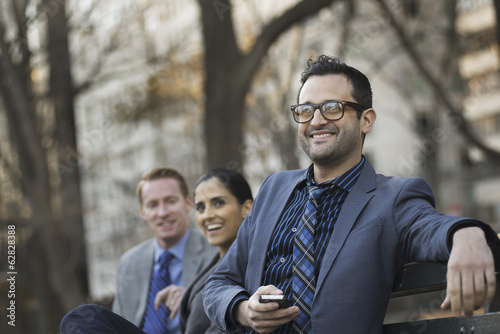 Business people in the city. Three people, two men and a woman in a city park relaxing.