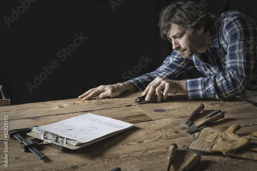 A man working in a reclaimed lumber yard workshop. Holding tools and sanding knotted and uneven piece of wood.