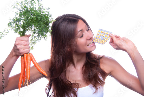 woman hold organic fresh carrots and eat medical tablet pills