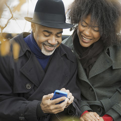 City life. Two people, a man and woman standing side by side, keeping in contact, using mobile phones, and checking the screen, laughing.
