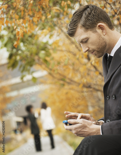 City life. A man in the park checking and texting, keeping in contact, using a mobile phone.