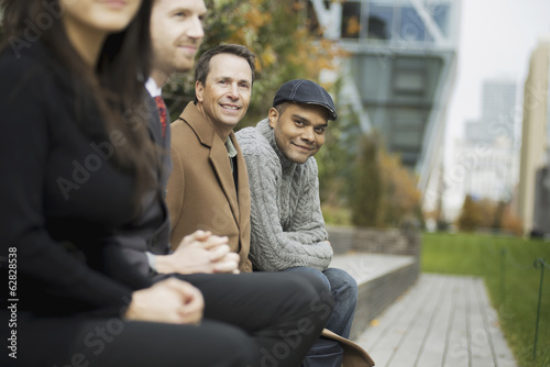 City life. A group of people on the go, keeping in contact, sitting on a bench. Men and women.