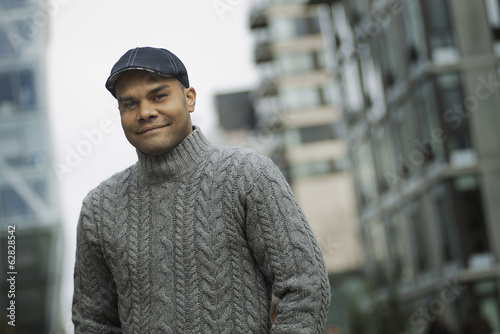 City life. A man in a flat hat, and jumper on the street of a city.
