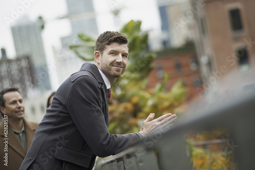 City life. A man in a winter coat leaning on a railing, taking time out. City landscape of buildings.