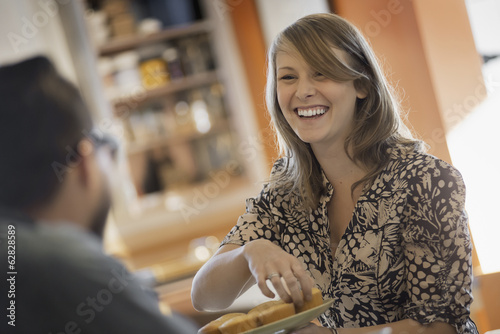 A couple sitting in a coffeeshop smiling and talking over a cup of coffee.