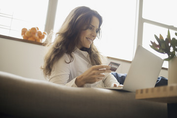 Woman on-line shopping on laptop on sofa with credit card