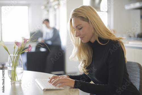 Couple relaxing at home, woman using keyboard