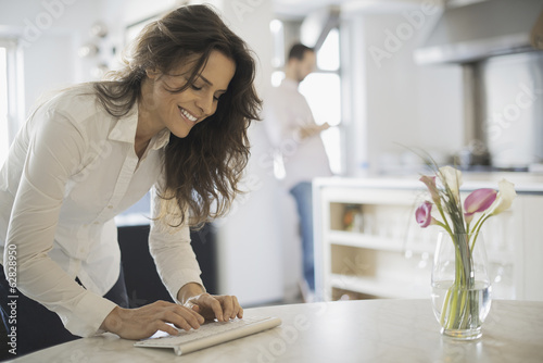 Couple relaxing at home, woman using keyboard, man using smartphone